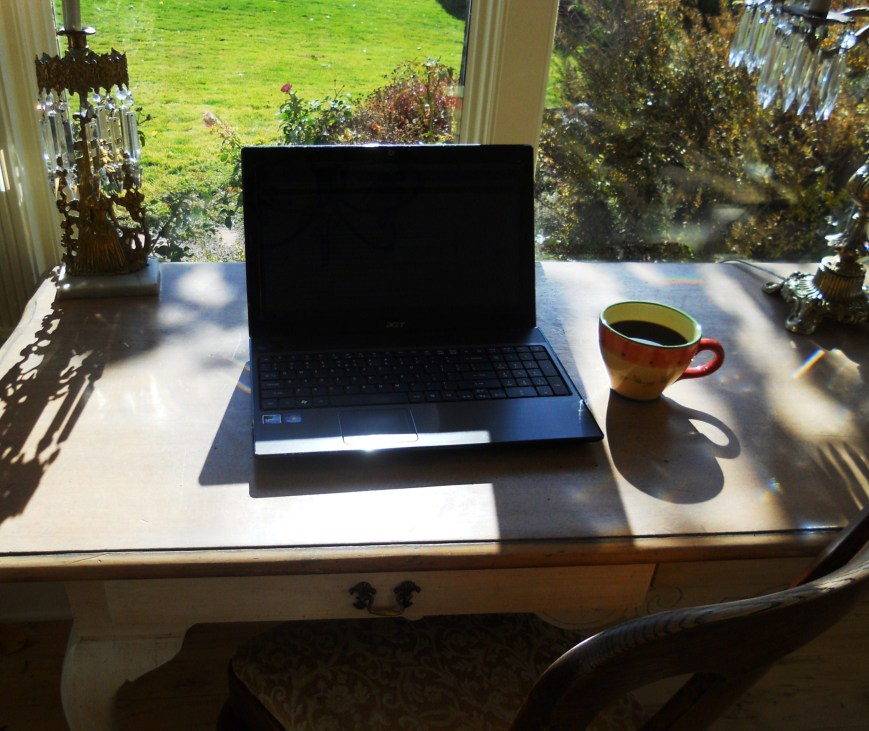 computer on table with coffee cup