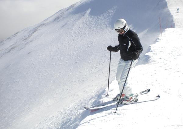 on the edge of a steep ski run looking down