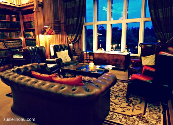 Library in Dalhousie Castle with sumptuous leather furniture, books and view of grounds