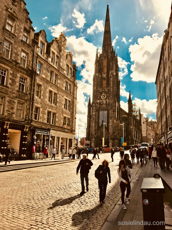 People walk down cobbled Royal Mile in Edinburgh Scotland, church background