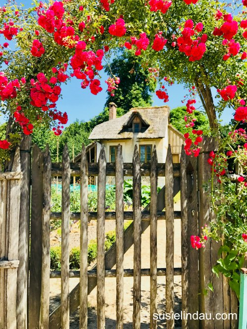 The Best of Versailles - Garden gate with arched trellised roses and cottage