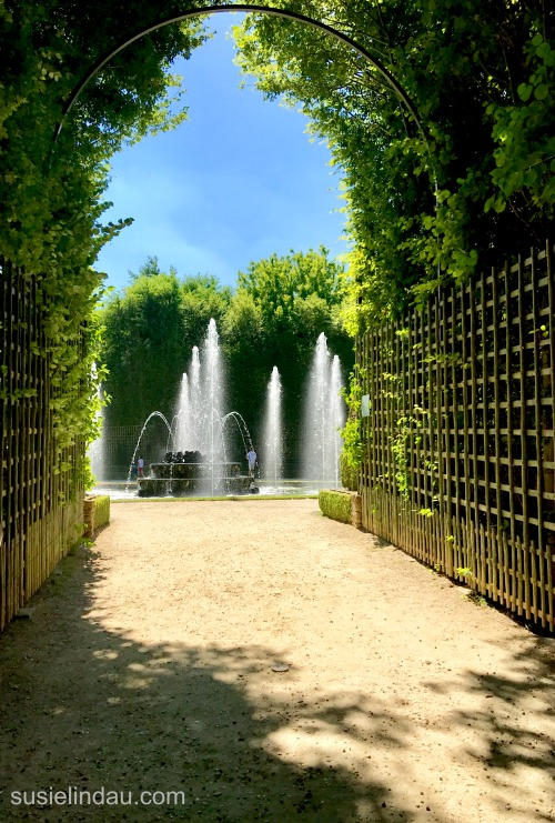 The Best of Versailles - Fountains peek through branched archway while music plays