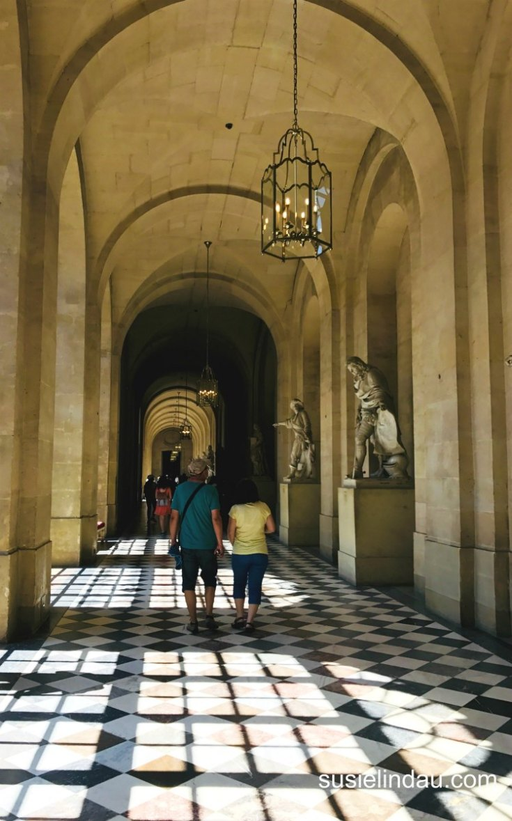 The Best of Versailles play of light on patterned floors in hallway under arched ceilings