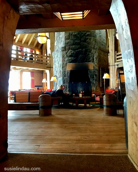 Timberline Lodge interior shot showing hand-hewn logs and massive stone fireplace