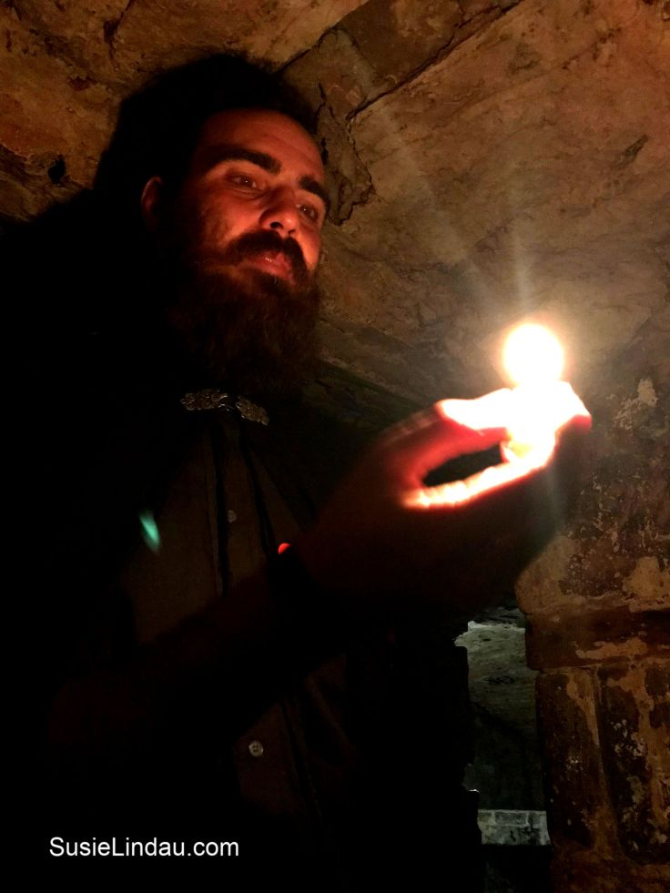 Mercat Ghost Tour Guide, Allen, holds a candle inside the Edinburgh Vaults. Click for photos of the tour! Edinburgh Ghost tour, Travel Edinburgh, Scotland, Travel Europe Destinations, Travel tips, Mercat tours, Travel Scotland #Travel #traveltips #bucketlist #ghosttours #Edinburghvaults