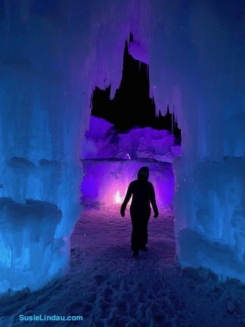 Ice Castles 22 Ice castle alienlike person walking in the glow of a fountain