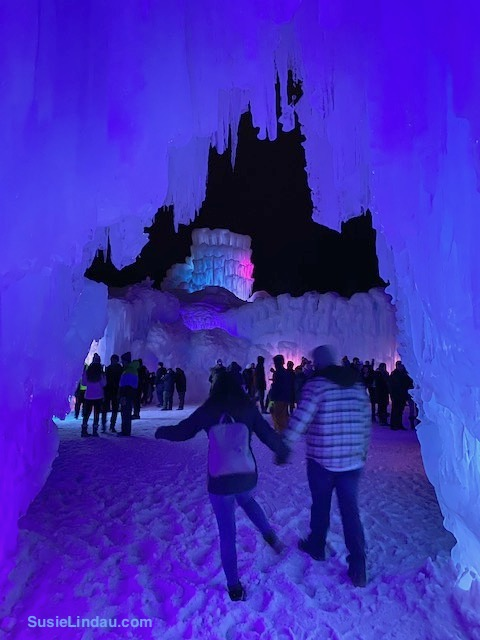 Ice Castles 4 A couple walks through a blue and purple ice castle