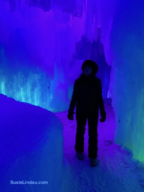 Ice Castles 7 Susie walking through a purple, green and blue ice castle