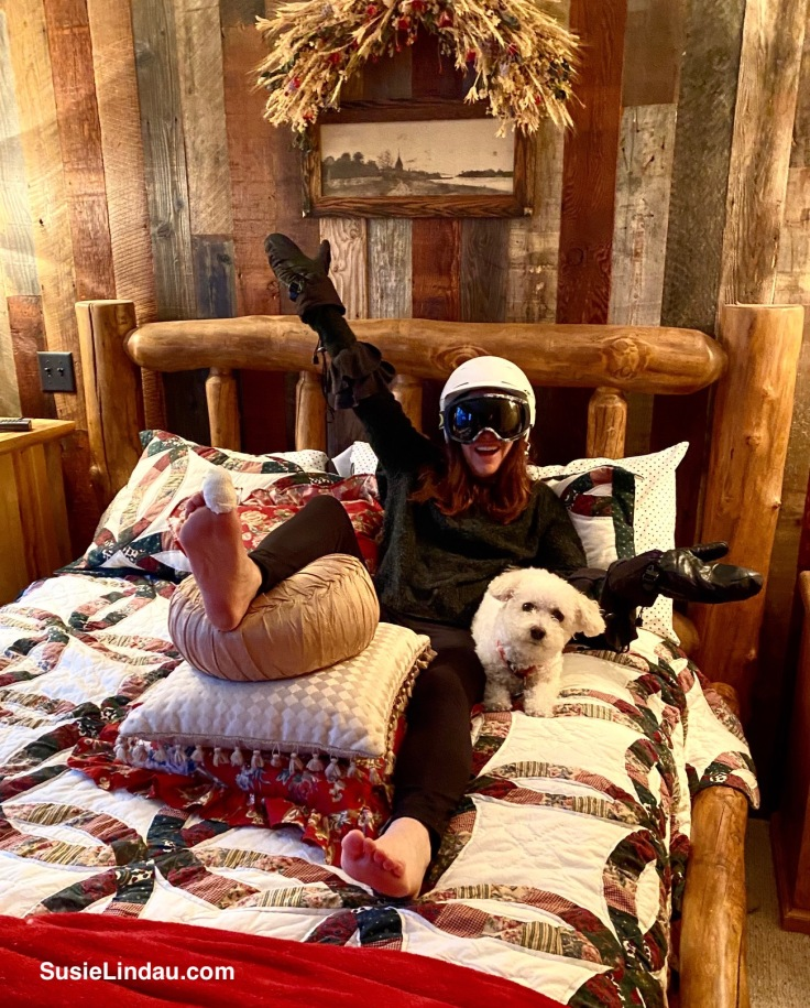Ready for skiing after injury - Woman elevating big toe while in bed with her white dog. she's wearing a helmet, goggles and ski mittens