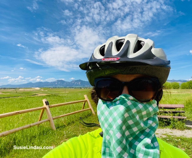 Susie Lindau biking during COVID with sunglasses, helmet and mask, flatirons in background