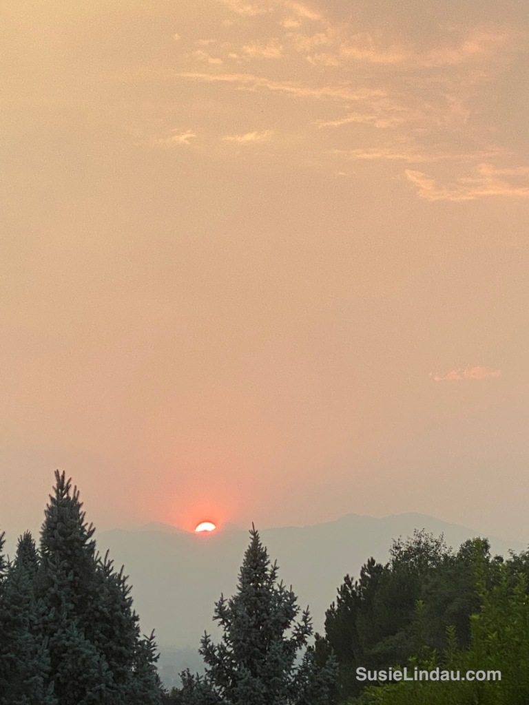 A thick, hazy, orange sunset over the foothills of Boulder, Colorado. The smoke from forest fires.